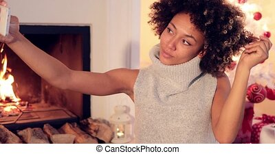 Elegant young woman taking a Christmas selfie posing in...