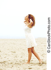 Elegant young woman walking on sand with hands in hair