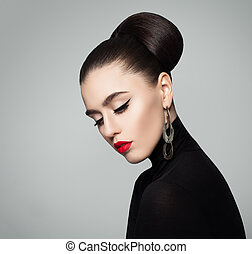 Elegant Young Woman with Hair Bun Hairstyle and Eyeliner Make up. Female Model wearing Black Roll Neck Jumper.
