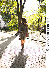 Elegant young woman with long hair in knit dress and warm coat walking in the park in sunny day