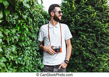elegante, hipster, com, um, barba, e, um, câmera, andar, ao redor, cidade, com, um, câmera