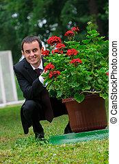 elegante, homem, em, paleto, sentando, perto, bush, de, flores