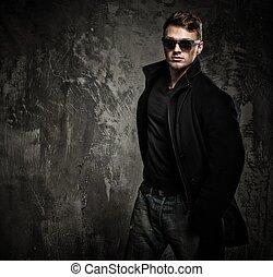 elegante, joven, en, abrigo negro, y, gafas de sol