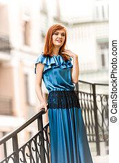 elegante, mujer, en, largo, vestido azul, posar, en, calle