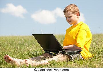 elegante, niño, con, un, computador portatil, en la hierba
