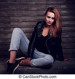 elegante, urbano, assento mulher, ligado, a, pedra, em, revestimento preto, azul, calças brim, com, expressivo, cara, parede, experiência escura