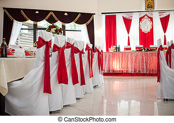 Elegantly catered wedding reception hall with red ribbons on luxury white chairs and marble floor
