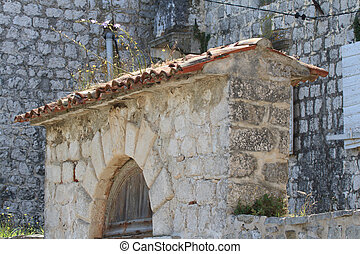 Element of a stone fence. Arch over the gate