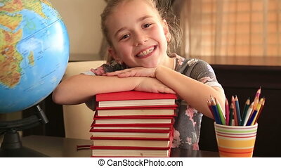 Elementary age girl posing on a stack of books.