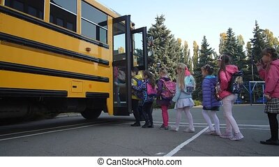 Elementary age students entering school bus - Lined up ...