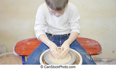 pottery wheel - elementary child shaping clay on pottery...