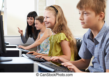 Elementary Pupils In Computer Class With Teacher