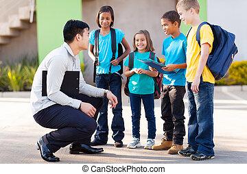 elementary pupils outside classroom talking to teacher -...