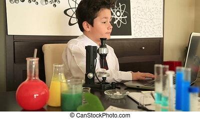 Elementary school boy studying chemistry - Schoolboy...