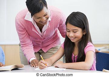 Elementary school clasroom with teacher - Teacher helping...