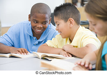 Elementary school classroom - Two boys discussing book...