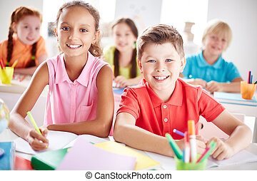 Elementary school learners - Two friendly schoolkids looking...