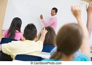 Elementary school maths class - Teacher holding elementary...