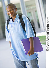Elementary school pupil outside carrying folder