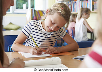 Elementary School Pupil Working At Desk In Classroom