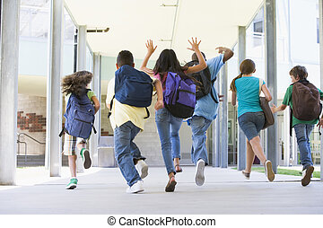 Rear view of elementary school pupils running outside