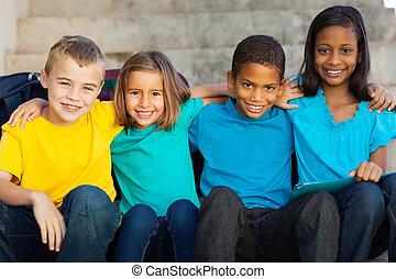 beautiful elementary school students sitting outdoors