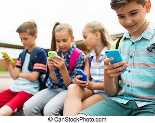 elementary school students with smartphones - primary...