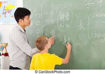 elementary school teacher helping young boy writing Chinese...
