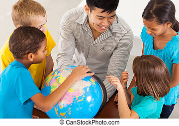 cheerful elementary school teacher with a globe teaching geography