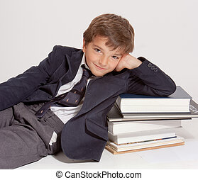 Cute young schoolboy lying on top of a pile of books