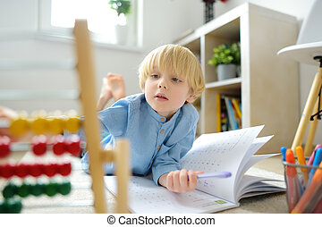 Elementary student boy doing homework at home. Child learning to count, solves arithmetic examples, using abacus. Math tutorial. Preparing preschooler baby for school. Education