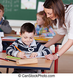 Elementary students - Teacher helping elementary student at...