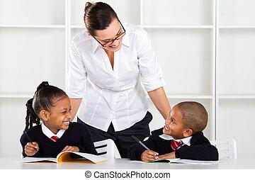 elementary teacher talking to pupil