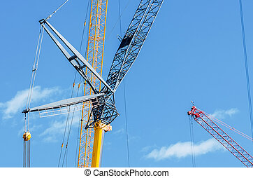 Elements of a part of the cranes on the construction site and the blue sky.