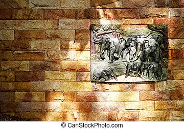 Elephant family art on sandstone on granite stone wall