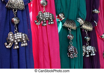 Crystal encrusted elephant jewelry hanging from bright, colorful scarves at bazaar.