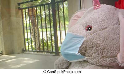 Slow motion of camera moving towards an elephant stuffed animal wearing a face mask while sitting by a window
