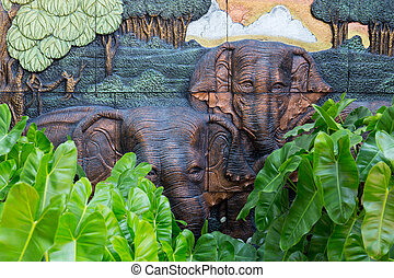 Elephants stone sculpture on the wall with jungle background in public garden, Thailand