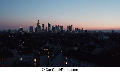 Elevated evening cityscape from drone in blue hour. Downtown panorama with skyscrapers against pink blue sunset sky. Frankfurt am Main, Germany. 4K.