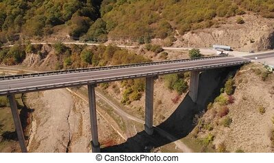 Elevated highway bridge providing road access over the dry gorge of the Arkala River near Ananuri Castle, from an Aerial Perspective. 4k Ultra HD video