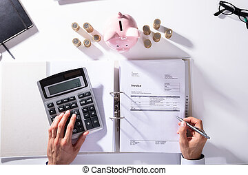 Elevated View Of Businessman Calculating Invoice With Piggybank And Coins On Desk