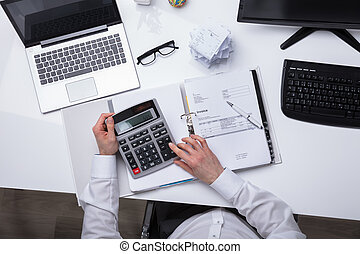 Elevated View Of A Businessperson's Hand Calculating Invoice With Calculator