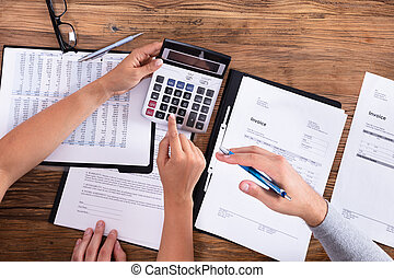 Elevated View Of Couple Calculating Bill With Calculator On Wooden Background