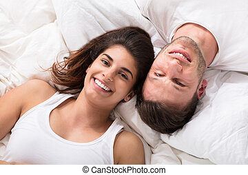 Elevated View Of Smiling Young Couple Lying On Bed