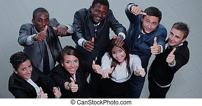Elevated view of large group of multiethnic business people cheering and showing thumbs up.