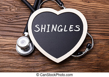 Elevated View Of Stethoscope And Heart With Word Shingles On Wooden Background