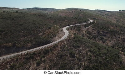 Elevating over cyclist on high slope mountain road - High...