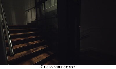 Elevator coming down in dark entrance hall - Darkness with...