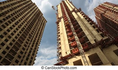 Elevator moves upward on unfinished skyscraper, view from...
