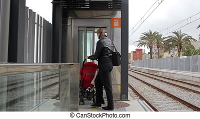 Elevator on the railway station. - Young mother with her...